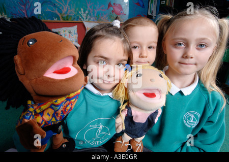 three 3 children in school uniforms with puppet dolls in a classroom - Stock Photo