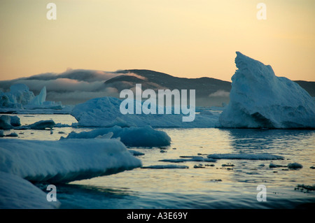 Evening red and mountains with mist above water with ice-pack and icebergs Sermilik Fjord Eastgreenland - Stock Photo