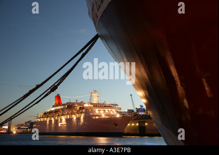 New Zealand, Wellington. Cruise Liner Nippon Maru in port at dusk, seen past bow  of freighter - Stock Photo