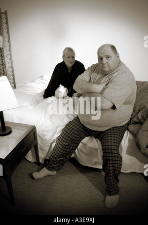 Husband and wife in their bedroom. - Stock Photo