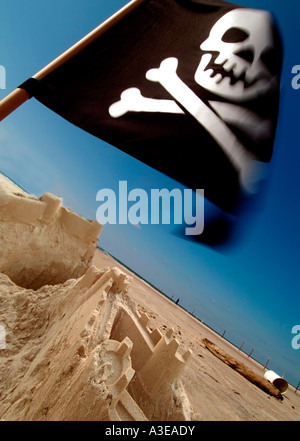 Sand castle with a Jolly Roger at a beach - Stock Photo