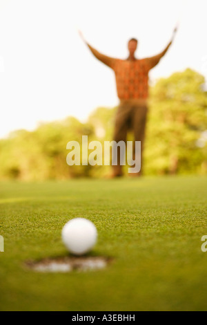 Close-up of a golf ball on the edge of a hole with a man raising his arms in the background - Stock Photo