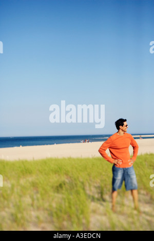 Mature man standing on the beach with his arms akimbo - Stock Photo