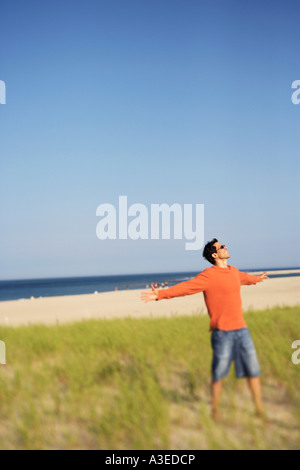 Mature man standing on the beach with his arms outstretched - Stock Photo