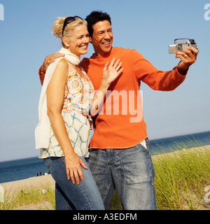 Mature couple taking a picture of themselves on the beach - Stock Photo