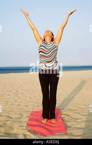 Mature woman exercising on the beach - Stock Photo
