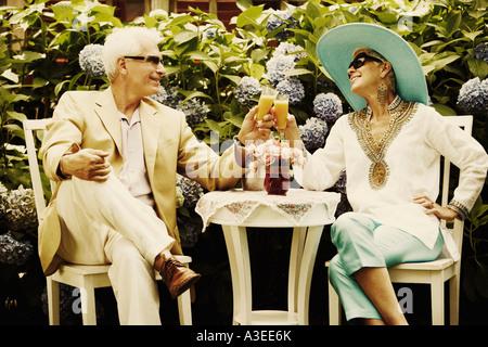 Close-up of a mature man and a senior woman sitting together and holding glasses of juice - Stock Photo