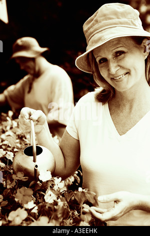 Portrait of a mature woman watering plants with a mature man in the background - Stock Photo