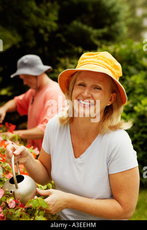 Portrait of a mature woman watering plants and smiling - Stock Photo