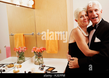 Portrait of a mature man and a senior woman embracing each other in the bathroom - Stock Photo