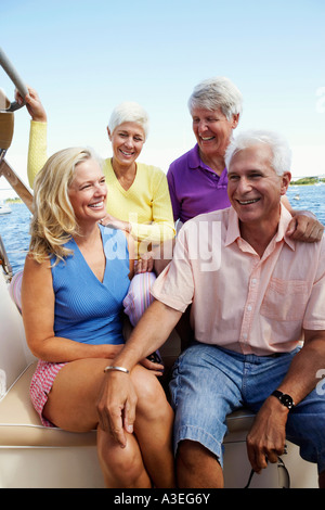 Close-up of two mature couples sitting in a boat and smiling - Stock Photo