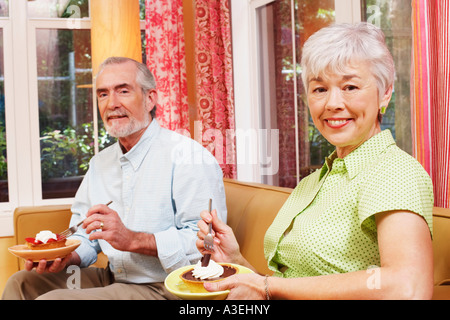 Portrait of a mature man and a senior woman eating a tart - Stock Photo