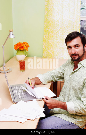 Portrait of a mature man sitting in front of a laptop and holding a document - Stock Photo