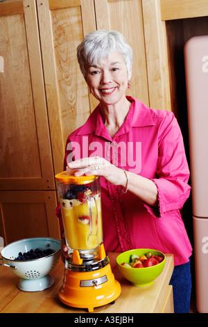 Portrait of a senior woman preparing mango shake in the kitchen - Stock Photo