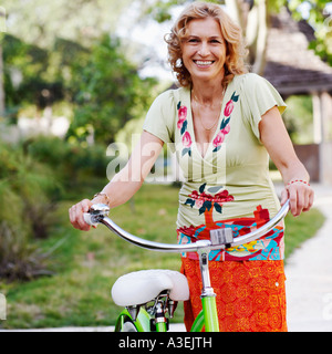 Portrait of a mature woman standing with a bicycle - Stock Photo