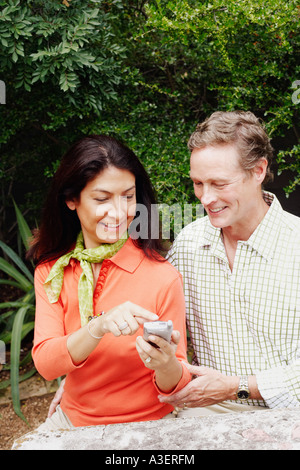 Close-up of a mature woman showing a mobile phone to a mature man - Stock Photo