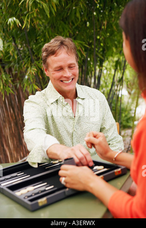 Close-up of a mature man playing backgammon with a mature woman - Stock Photo