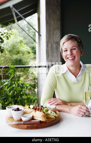 Portrait of a mature woman holding a champagne flute and smiling - Stock Photo
