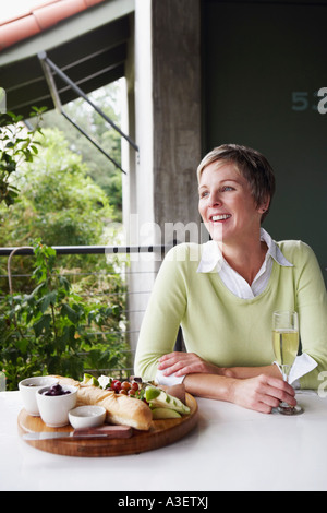 Mature woman holding a champagne flute and smiling - Stock Photo