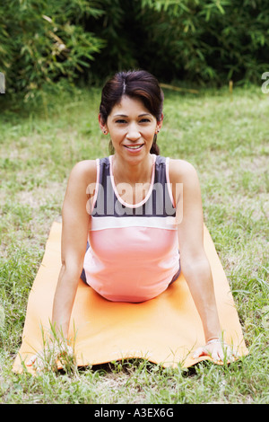 Portrait of a mature woman doing yoga on the lawn - Stock Photo