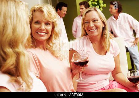 Three women sitting together and smiling - Stock Photo