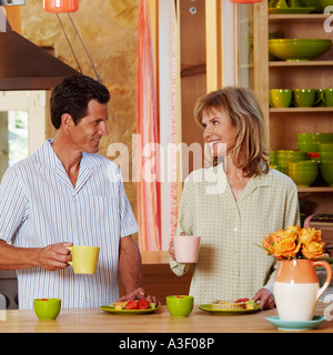 Mature couple holding cups in the kitchen and smiling - Stock Photo