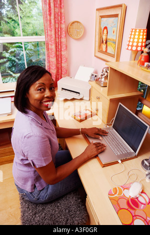 Portrait of a mature woman using a laptop and smiling - Stock Photo