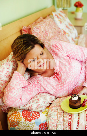 High angle view of a mature woman lying on the bed and holding a plate of cake - Stock Photo