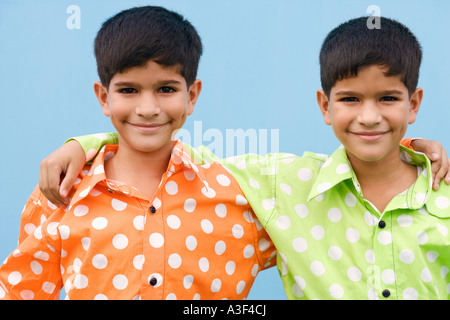Portrait of twin brothers with their arms around each other - Stock Photo