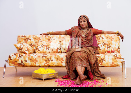 Portrait of a bride sitting on a couch - Stock Photo