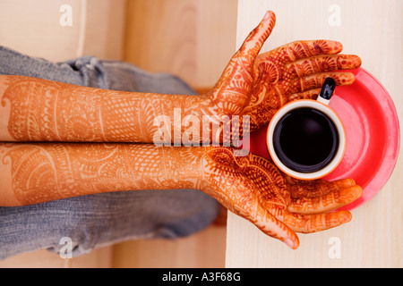 Close-up of a woman's henna tattooed hands holding a cup of tea - Stock Photo