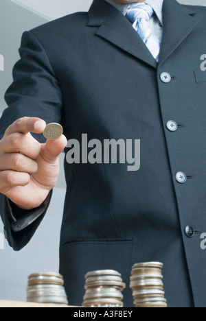 Mid section view of a businessman holding a coin - Stock Photo