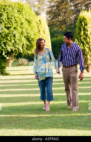Mid adult man and a young woman holding each other's hands and walking in a park - Stock Photo