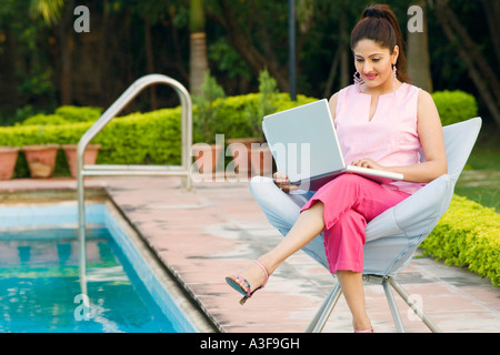 Young woman using a laptop at the poolside - Stock Photo