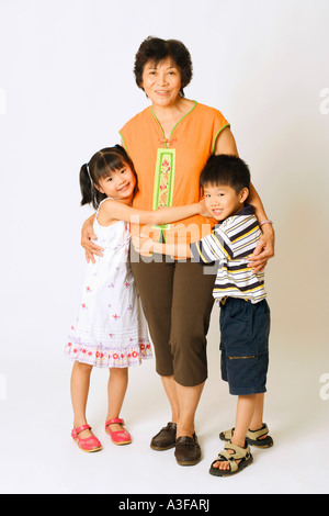 Portrait of a mature woman standing with her grandson and a granddaughter