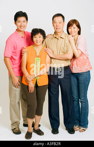 Portrait of a young couple standing with their parents - Stock Photo