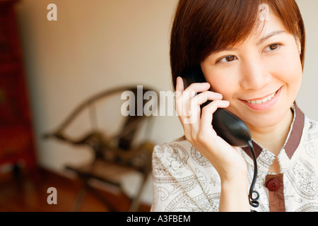 Close-up of a young woman talking on the telephone - Stock Photo