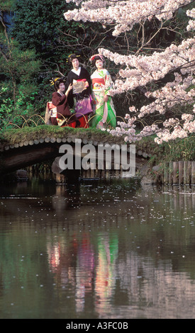 Geisha girls in colorful kimonos on bridge over pond reflecting cherry blossoms in Tokyo park - Stock Photo