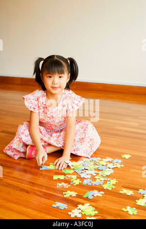 Portrait of a girl playing with a jigsaw puzzle - Stock Photo