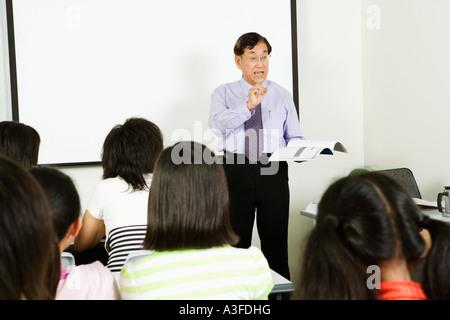Teacher teaching in a classroom - Stock Photo