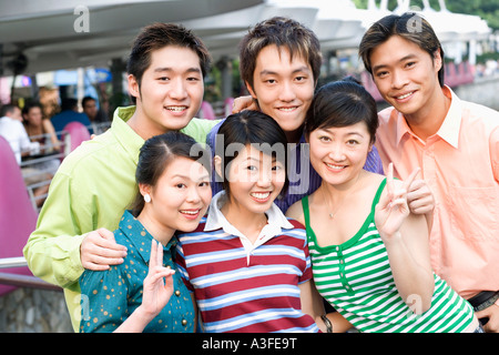 Portrait of a group of people standing together and smiling - Stock Photo