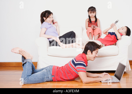 Young woman and her son and daughter sitting on a couch with a mid adult man lying on the floor with a laptop - Stock Photo