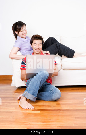 Young woman sitting on a couch with a mid adult man using a laptop - Stock Photo