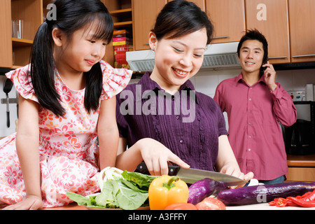 Close-up of a young woman cutting vegetables with her daughter sitting beside her - Stock Photo