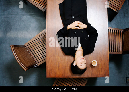 High angle view of a businesswoman lying on the table - Stock Photo
