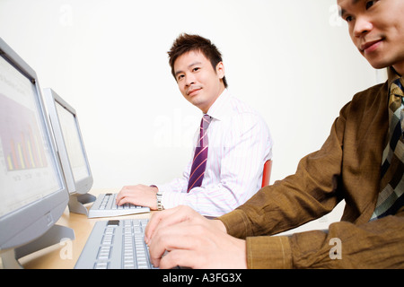 Two businessmen working on computers - Stock Photo