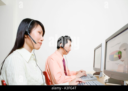 Two customer service representatives working on a computer - Stock Photo