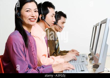 Three customer service representatives working on computers - Stock Photo