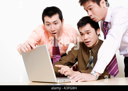 Three businessmen using a laptop and looking surprise - Stock Photo