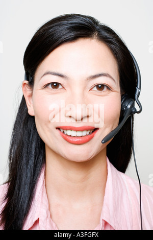 Portrait of a female customer service representative using a headset - Stock Photo
